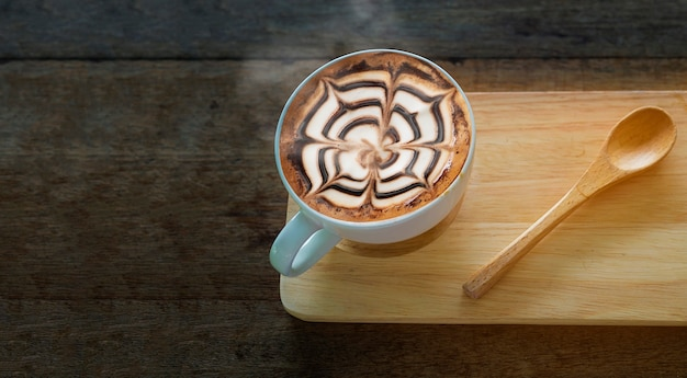 Taza de café caliente con una bonita decoración de arte latte en una vieja mesa de textura de madera