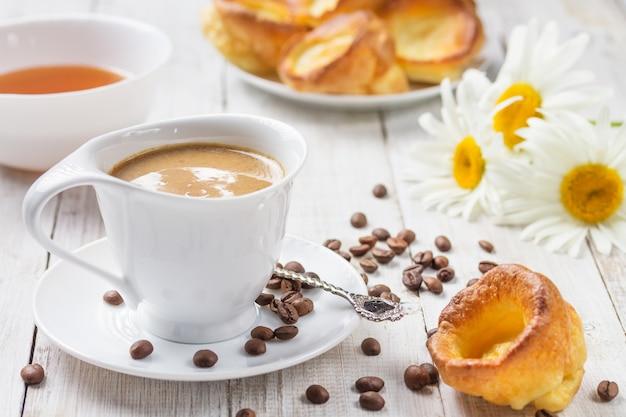Una taza de café caliente con budines de yorkshire y haney, y margaritas en una mesa de madera blanca. desayuno