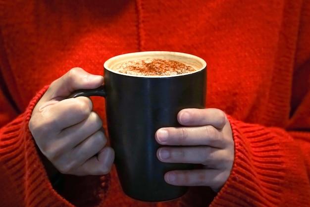 Taza de café caliente en el concepto de mano, comida y bebida de las mujeres