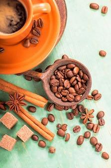 Taza de café caliente con espuma de leche, canela, anís estrellado y granos de café en la mesa de madera