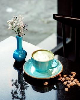 Taza de café caliente con espuma y pistachos