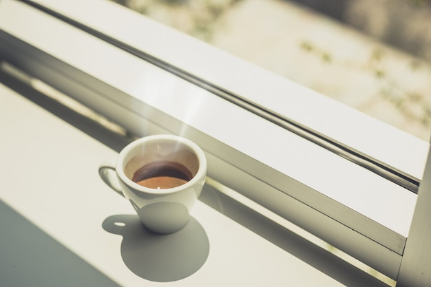 Taza de café caliente exprés puesta en mesa cerca de la ventana