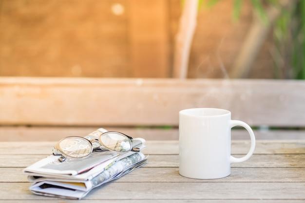 Taza de café caliente, gafas para leer y periódico o.