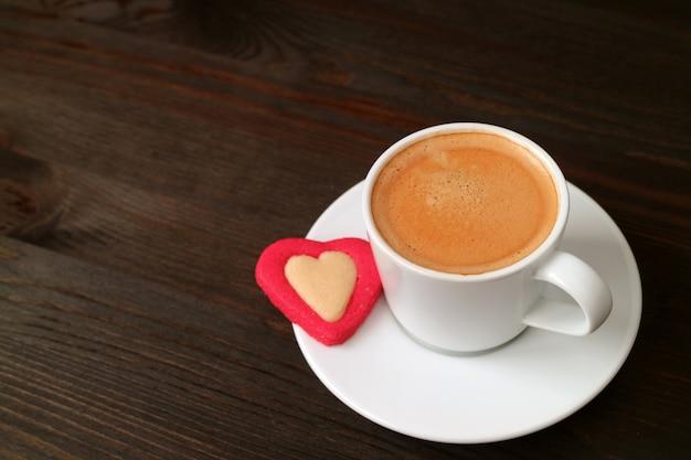 Taza de café caliente con una galleta en forma de corazón en la mesa de madera marrón oscuro