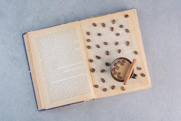 Taza de café caliente con granos de café en libro abierto.
