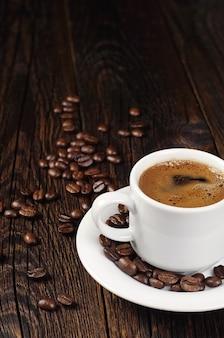 Taza de café caliente y granos de café en la mesa de madera