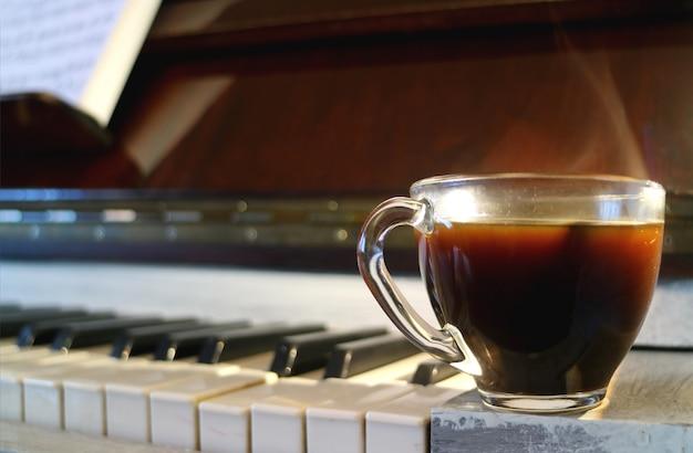 Taza de café caliente con humo con el teclado del piano borroso en segundo plano.