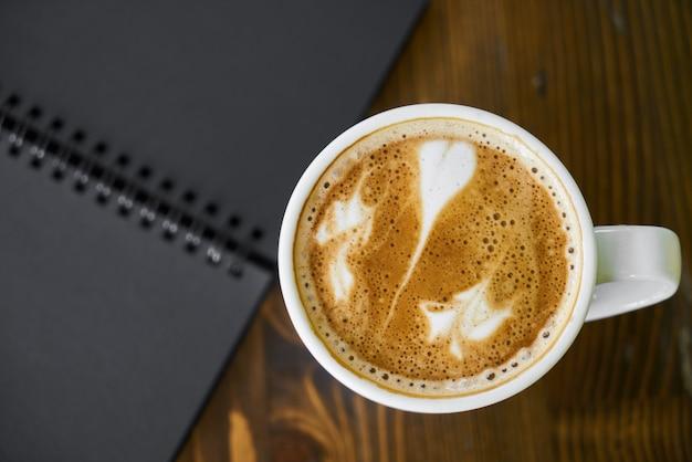 Taza de café caliente con leche en una mesa de madera