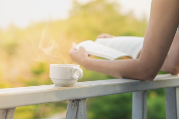 Taza de café caliente con mujer leyendo libro al aire libre
