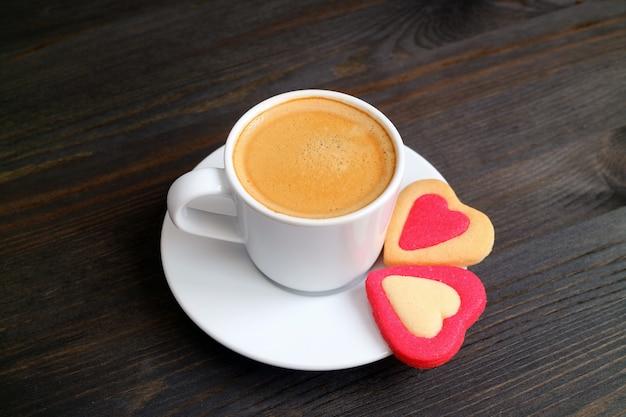 Taza de café caliente con un par de galletas en forma de corazón en la mesa de madera de color oscuro