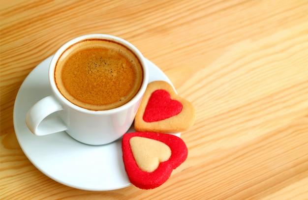 Taza de café caliente con un par de galletas en forma de corazón en la mesa de madera con espacio de copia