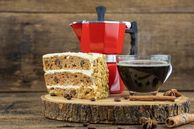 Una taza de café caliente con pastel y cafetera italiana (moka) en mesa de madera.