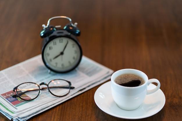 Taza de café caliente con periódico por la mañana.