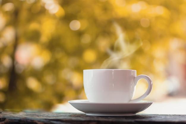 Taza de café caliente sobre la naturaleza otoño