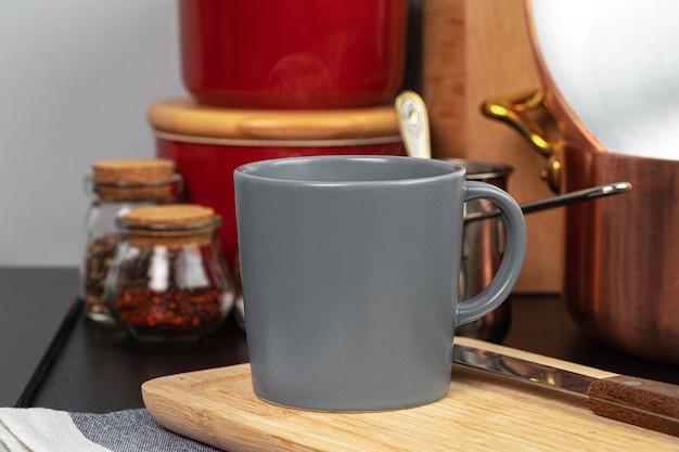 Taza de café caliente sobre una plancha de madera en la mesa de la cocina de cerca