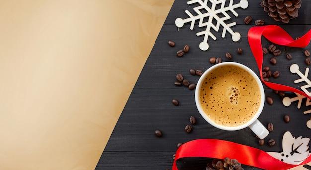 Taza de café caliente sobre una superficie de madera negra en navidad