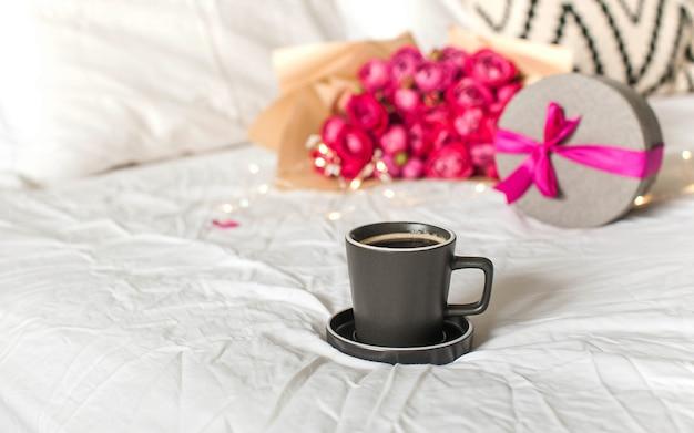 Taza de café en la cama en el fondo de un ramo de flores un concepto de regalo del día de san valentín marzo ...