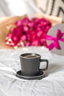 Taza de café en la cama sobre la superficie de un ramo de flores y un regalo