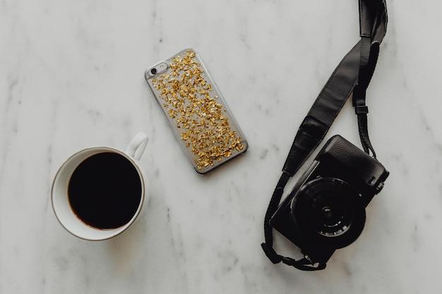 Taza de café con una cámara réflex digital y un teléfono.
