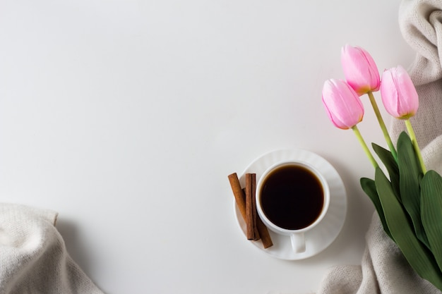 Taza de café, canela, bufanda, tulipanes en la superficie blanca. concepto de primavera vista plana, vista superior