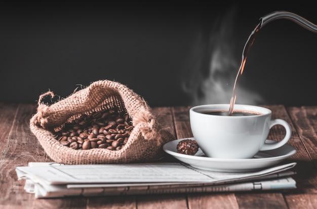 Taza de café, canela, café tostado en grano y periódico en la mesa de madera