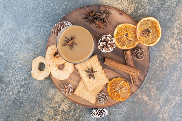 Taza de café con canela y piñas en placa de madera. foto de alta calidad