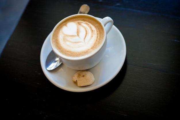 Taza de café cappuchino o café con leche en una taza blanca con espuma en forma de corazón y galletas