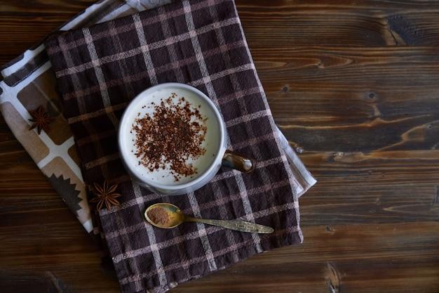 Taza de café capuchino con canela y granos de café en copyspace de madera vista superior.