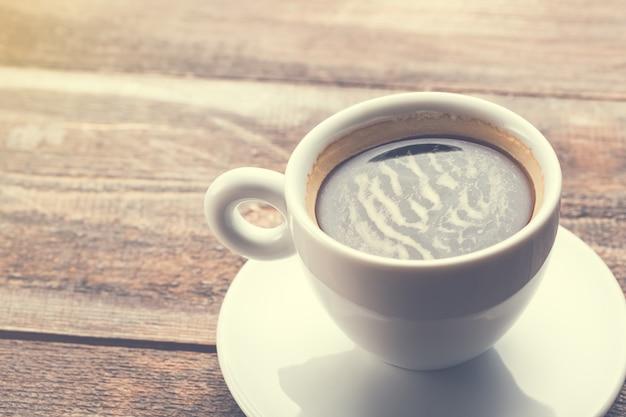 Taza de café capuchino en mesa de madera