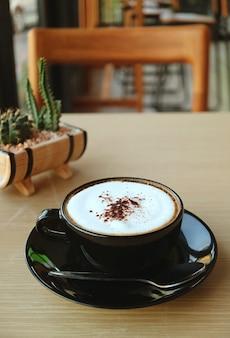 Taza de café capuchino con planta suculenta en maceta borrosa en el telón de fondo