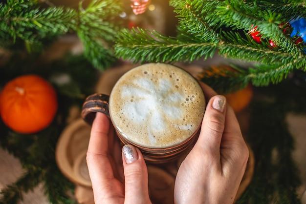 Taza de café capuchino con ramas verdes de un árbol de navidad