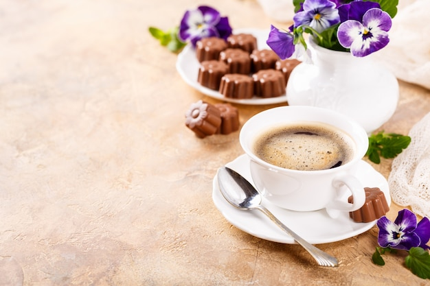 Taza de café con caramelos de chocolate.