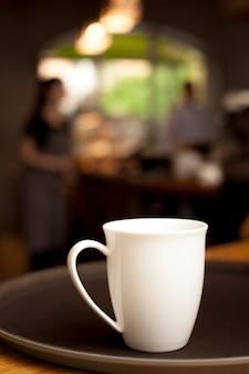 Taza de café de cerámica blanca en bandeja en cafetería
