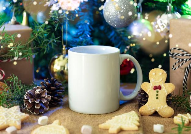 Taza de café de cerámica blanca y decoración de navidad en el fondo de la tabla de woon. maqueta para mensajes de texto publicitarios creativos o contenido promocional.