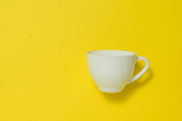 Taza de café de cerámica blanca sobre un fondo amarillo. platos para bebidas calientes.