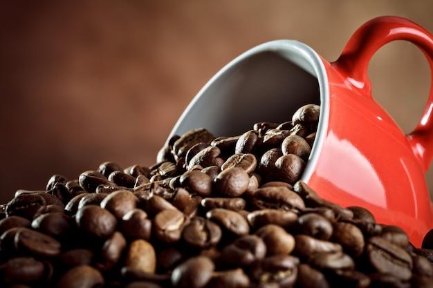 Taza de café de cerámica roja en granos de café caliente.