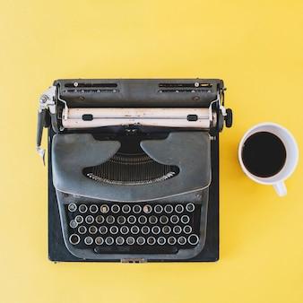 Taza de café cerca de la máquina de escribir