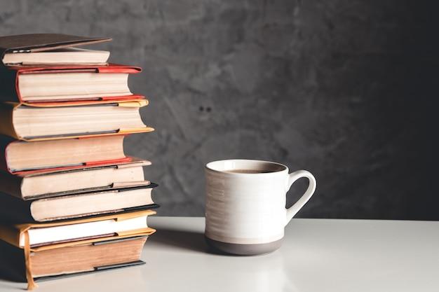 Una taza de café cerca de la pila de libros sobre fondo gris