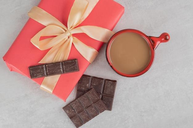 Taza de café, chocolate y caja de regalo sobre superficie de mármol
