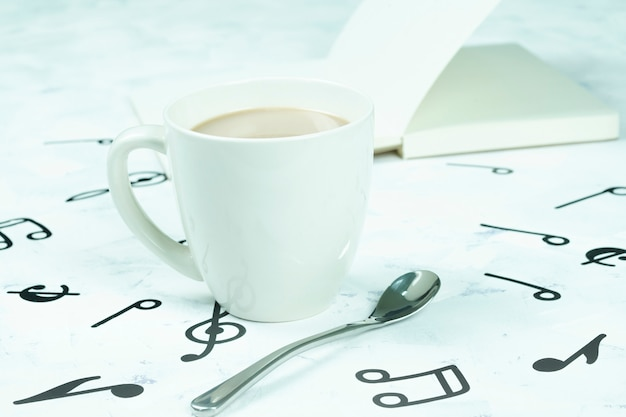 Taza de café colocada en el piso, patrón de nota musical