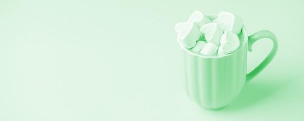 Taza de café color menta y malvaviscos en forma de corazón