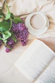 Taza de café de composición romántica por la mañana con un libro y un ramo de lilas en la cama
