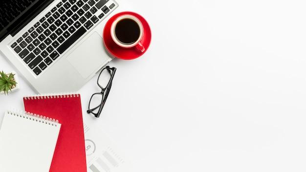 Taza de café en la computadora portátil con las lentes y la libreta espiral en el fondo blanco