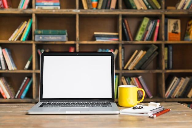 Taza de café y computadora portátil con papelería en el escritorio de madera en la biblioteca