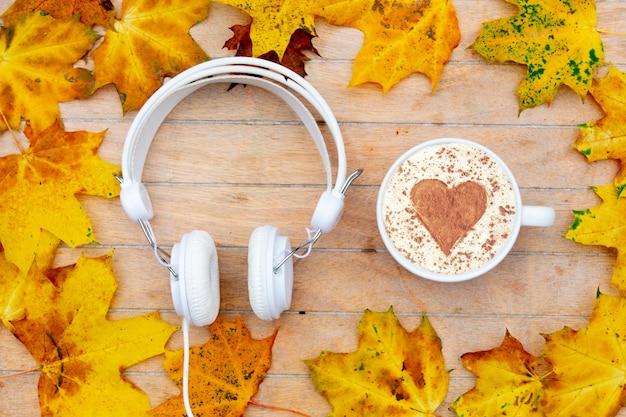 Taza de café con un corazón de canela y auriculares sobre la mesa, hojas de arce alrededor