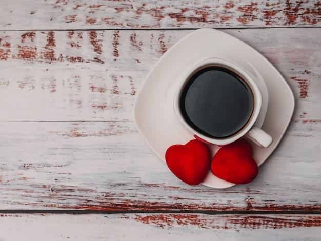 Taza de café y corazones en la mesa de madera. concepto de la mañana desayuno en el día de san valentín