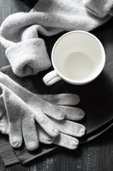 Taza de café y cosas tejidas a mano sobre una superficie negra