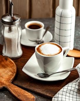 Una taza de café con crema y azúcar.