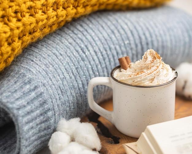 Taza de café con crema batida y suéteres