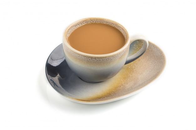 Taza de café con crema en placa de cerámica aislada, vista lateral.